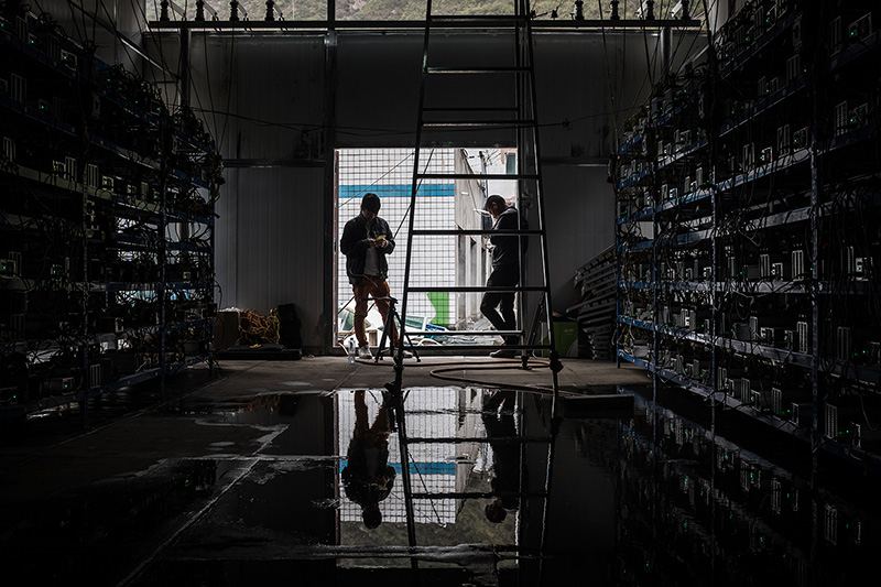 "Employees use their phones at the Bitcoin mine, September 26, 2016. The mine has 550 ""mining machines"" running continuously. They solve complicated mathematical problems for which they are rewarded with Bitcoins. Seven employees work in shifts monitoring the machines to keep the mine running 24 hours a day."