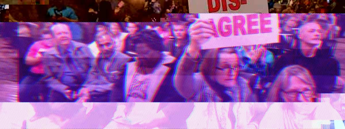 conference session with someone holding up a sign saying 'dis-agree'